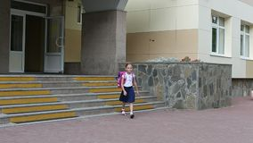 Young girl with backpack go out from school downstairs. A girl in school uniform comes out of the school and descends stock footage