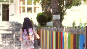 Young girl with backpack is going back to school. Happy student girl with backpack going back to school stock video footage