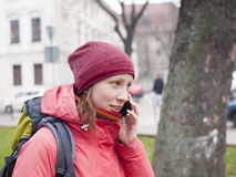 A young girl with a backpack and phone. Stock Image