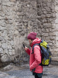 A young girl with a backpack and phone. Stock Photography