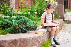 Young girl with bagpack reads waiting for school Stock Photos