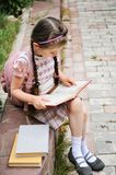 Young girl with bagpack reads waiting for school Royalty Free Stock Image