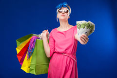 Young girl with bags and bunch of money in the hands of. Young girl with bags and bunch of money in the hands on a blue background Royalty Free Stock Images