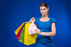 Young girl with bags and bunch of money in the hands of. Young girl with bags and bunch of money in the hands on a blue background Stock Image