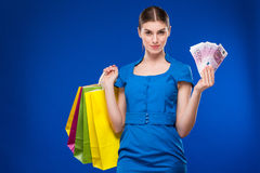 Young girl with bags and bunch of money in the hands of. Young girl with bags and bunch of money in the hands on a blue background Royalty Free Stock Photos