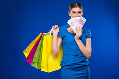 Young girl with bags and bunch of money in the hands of. Young girl with bags and bunch of money in the hands on a blue background Stock Photo
