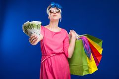 Young girl with bags and bunch of money in the hands of. Young girl with bags and bunch of money in the hands on a blue background Royalty Free Stock Photography