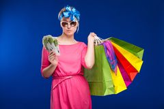 Young girl with bags and bunch of money in the hands of. Young girl with bags and bunch of money in the hands on a blue background Stock Photography
