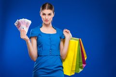 Young girl with bags and bunch of money in the hands of. Young girl with bags and bunch of money in the hands on a blue background Stock Photos