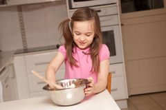 A young girl is baking in a kitchen Stock Photos