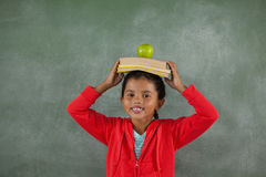 Young girl balancing books and apple on her head Royalty Free Stock Image