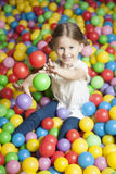 Young girl in ball pit throwing colored balls Royalty Free Stock Photos