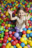Young girl in ball pit throwing colored balls stock photography