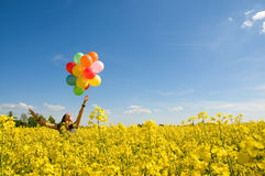 Young girl with balloons on canola field. royalty free stock image