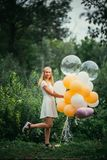 Young girl with balloons on nature background stock photos