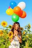 Young girl with balloons in a sunflower field Stock Images
