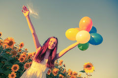 Young girl with balloons at a sunflower field Stock Photos