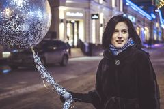Young girl with baloon walking in the night city streets royalty free stock photography