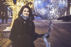 Young girl with baloon walking in the night city streets royalty free stock photos