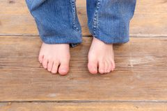 Young girl barefoot on wooden floor. Close up young girl barefoot on wooden floor Royalty Free Stock Photography