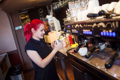 Young girl Barista prepares coffee in pub, bar Stock Photography
