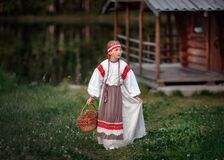 A young girl with a basket of Rowan berries in her hands against the background of the river and the Russian bath