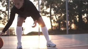 Young girl basketball player exercising on outdoor court. Bouncing the ball low at the ankle level, practicing. Sun. Shines on the background stock video