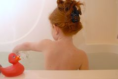 Young Girl in Bath. Young red haired girl sitting Stock Photo