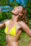 The young girl in a bathing suit drinking water Stock Images