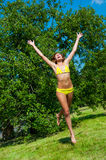 The young girl in a bathing suit jumping. In park Stock Photos