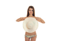 A young girl in a bathing suit stands directly looks into the camera and closes the chest Hat Royalty Free Stock Photography