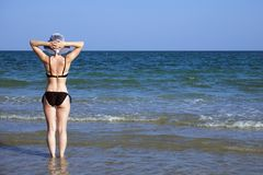Young girl in a bathing suit and a striped hat is standing in the sea holding her hands behind her head, fingers folded into the l. Ock. Standing back stock photography