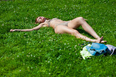The young girl in a bathing suit sunbathes. In park Royalty Free Stock Photo