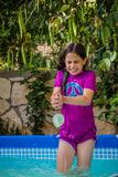 Young girl in a bathing suit try to catch water balloon Stock Photography
