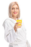 Young girl in a bathrobe holding an orange juice Stock Image