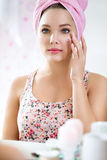 Young girl in bathroom front of mirror putting cream Stock Photos
