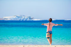 Young girl on the beach background big cruise liner. Woman enjoy her wekeend on one of the beautiful beaches in Greece Royalty Free Stock Photography