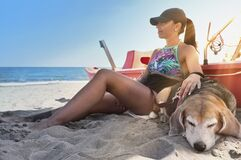 Young girl on the beach with the beagle dog