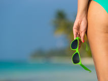 Young girl on a beach with glasses in hand on the tropical islan Royalty Free Stock Photos
