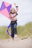 Young girl on beach with kite smiling royalty free stock images