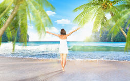 Young girl on the beach with palm trees Royalty Free Stock Images