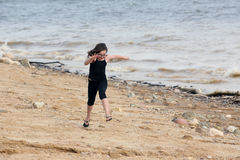 Young girl at the beach playing by the water Royalty Free Stock Photography
