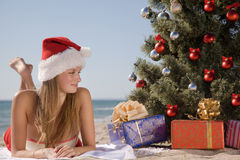 Young girl in the beach resort lying under the Christmas tree. In Santa hat Royalty Free Stock Images