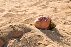 Young girl at the beach in sandbed Stock Photos