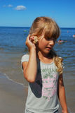 Young girl on beach with shell Stock Photography
