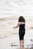 Young girl at the beach standing by the water Royalty Free Stock Images