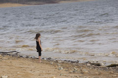 Young girl at the beach standing by the water Royalty Free Stock Image