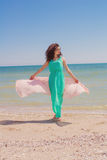 Young girl on the beach in summer  with a flying scarf Stock Photos