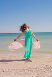 Young girl on the beach in summer  with a flying scarf Stock Photography
