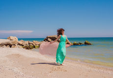 Young girl on the beach in summer  with a flying scarf Stock Image